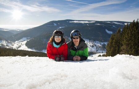chearful: Young happy couple lying in snowy mountains, czech