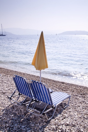 Sun lounger and umbrella on empty sandy beach photo