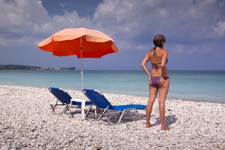 Sun lounger and umbrella on empty sandy beach with girl photo