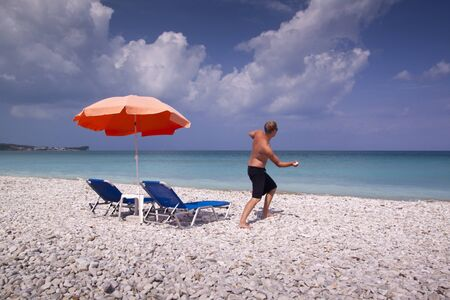 Sun lounger and umbrella on empty sandy beach with man photo