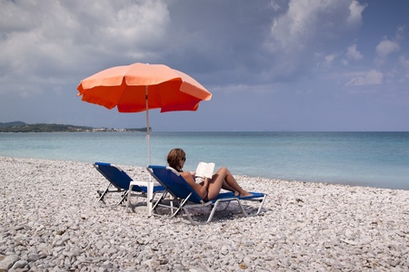 Sun longer and umbrella on empty sandy beach photo