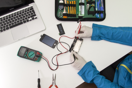 Prague, Czech Republic - NOVEMBER 30, 2014: Photo of the repair process of an iPhone 4. IPhone 4 are produced by Apple Computer, Inc..