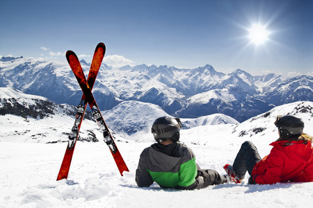 SKI: Young happy couple lying in snowy mountains with cross ski