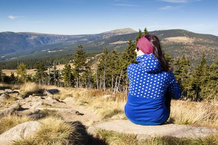 Girl with backpack looks out over the mountains, Czech mountains Krkonose Stock Photo