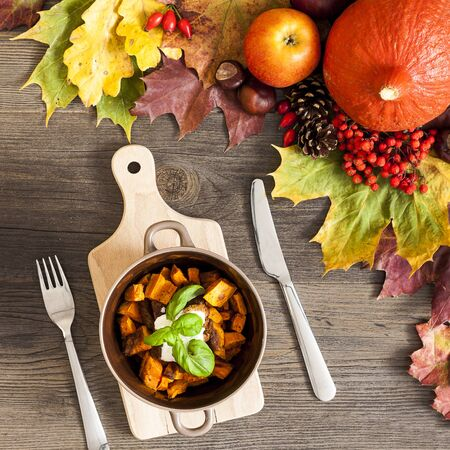 Roasted pumpkin with color autumn leaves over wooden background Stock Photo