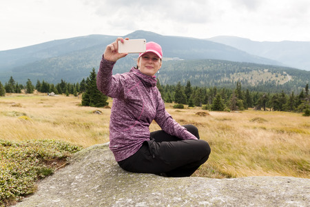 woman hiker taking photo selfie with smart phone at mountain krkonose