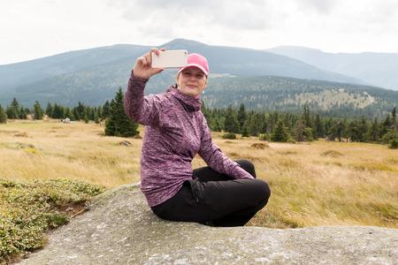 woman hiker taking photo selfie with smart phone at mountain krkonose