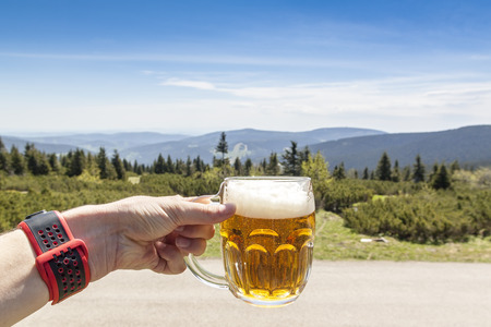 Man holding beer glass in mountain, Krkonose, Czech mountains Stock Photo