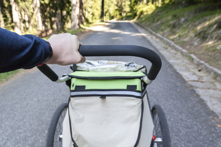Man walking and jogging outdoors with child jogging stroller