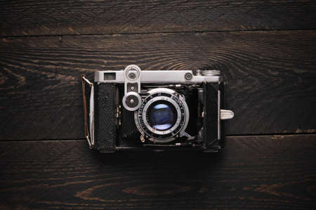 photographic camera: old vintage film photographic camera on a darkness wooden background