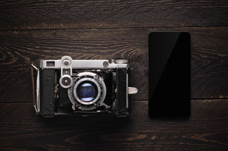 old vintage film photographic camera with black smart phone