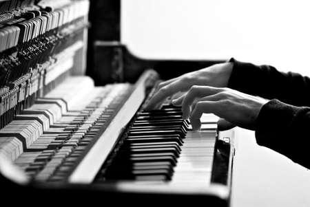 黒と白の古いピアノの鍵盤上のピアニストを手します。