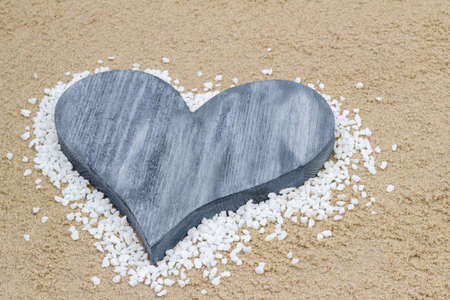 Handmade blue heart in the sand with copy space  photo