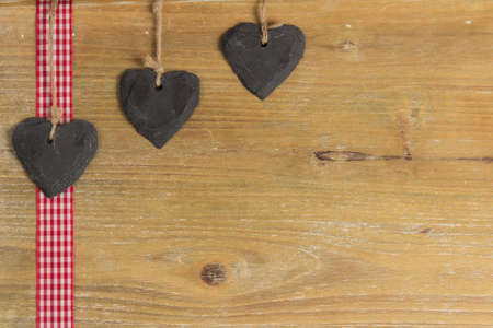 Slate heart lies on a red border  Behind an old wooden board  photo