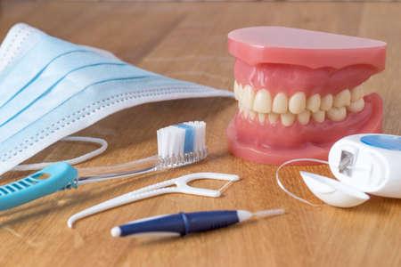 prosthodontics: Dentiera con strumenti dentali pulizia Compreso uno spazzolino, filo interdentale, mascherina usa e getta e strumento di plastica filo interdentale in concetto di igiene orale a
