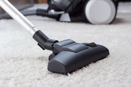 Close up of the head of a modern vacuum cleaner being used while vacuuming a thick pile carpet white