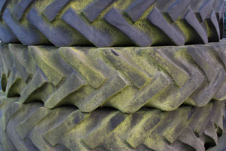 treads: Three old tire treads with green mold on the rubber stacked on top of one another, close up background texture
