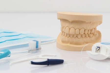 prosthodontics: Dentiera con strumenti dentali per la pulizia, tra cui uno spazzolino, filo interdentale, mascherina usa e getta e strumento di filo interdentale di plastica in un concetto di igiene orale