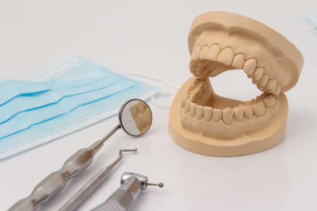 plaster mould: Open dental mold of teeth with dental implements including a disposable face mask, drill, mirror and pick in a dentistry, and healthcare concept Stock Photo