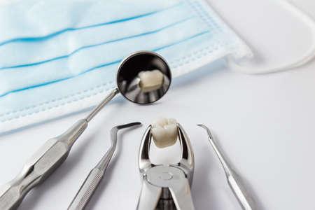 Concepto de la extracción del diente con un arsenal, ,, de herramientas dental de acero inoxidable y una máscara con el diente extraído abrochado en las pinzas y se refleja en el espejo