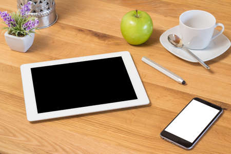 Conceptual White Teacup with Spoon on a Plate, Fresh Green Apple and Tablet and Mobile Phone Gadgets on Top of a Wooden Table with Small Flower Vase at the Corner. photo