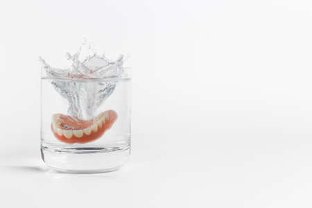 Single orthodontic dentures mold falling into clear glass of water with splash over white background next to copy space on side