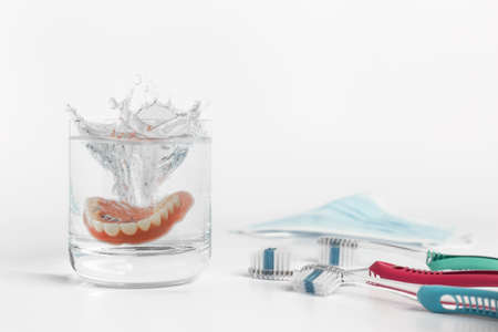 Dentures hygiene concept displaying mold falling and splashing into glass of water next to pair of toothbrushes and mask on white background Stock Photo