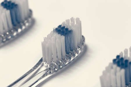 bristles: Selective focus close up of three clear toothbrush heads with white and blue bristles