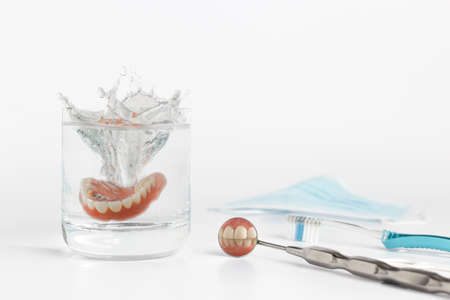 denture: Close up of teeth on dental hygienist mirror next to dentures being dropped in water among other tools on white background