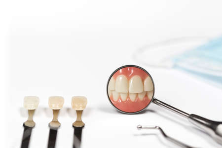 front teeth: Three teeth attached to metal rods next to dental pick and mirror displaying clenched front teeth besides mask on white table