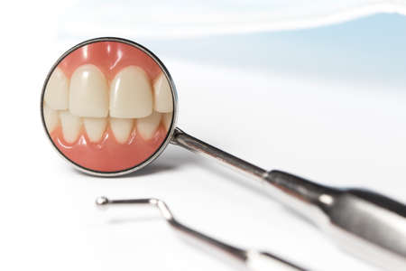 odontology: Dental mirror displays image of clenched front teeth beside metal pick and mask on white table