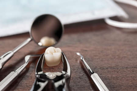 concepto de la extracción del diente con una serie de herramientas dental de acero inoxidable y una máscara con el diente extraído abrochado en las pinzas y se refleja en el espejo