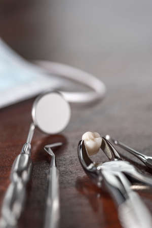tooth extraction: Tooth extraction concept with an array of stainless steel dental tools and a mask with the extracted tooth clasped in the pincers and reflected in the mirror