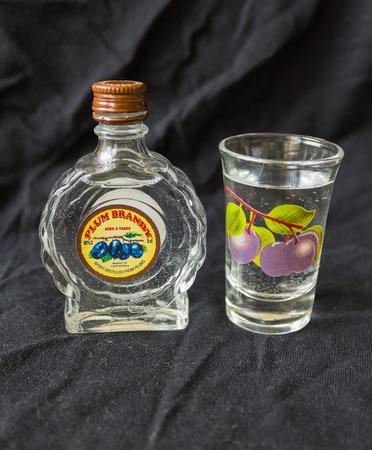 a small bottle of plum brandy on a dark background Reklamní fotografie
