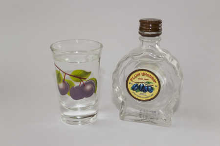 a small bottle of plum brandy on a white background