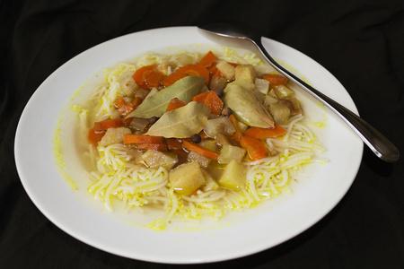 polévka na bílém talíři tmavém pozadí