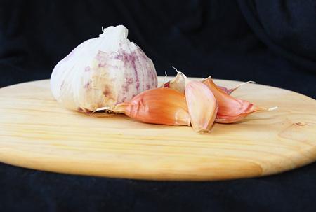 whole garlic cloves on a cutting board