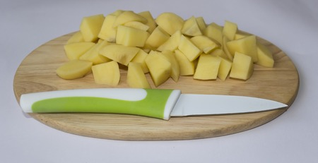 Group cubes of potatoes on wooden board with knife.