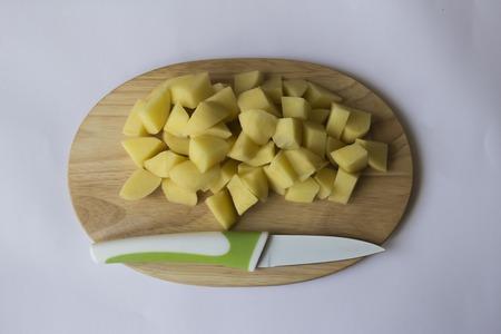 Skupina kostky brambor na dřevěné desce s nožem.