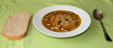 bean soup and bread on a green background