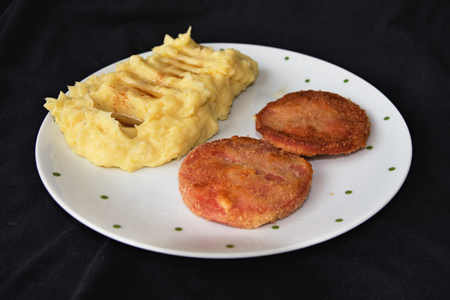 Mashed potatoes and breaded fried sausage dark background