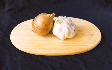 onions and garlic on a chopping board