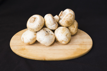 champignons on cutting board dark background Reklamní fotografie