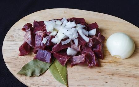 raw pork hearts sliced on a cutting board detail