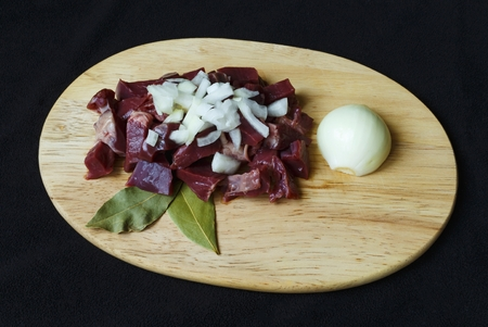 raw pork hearts sliced on a cutting board