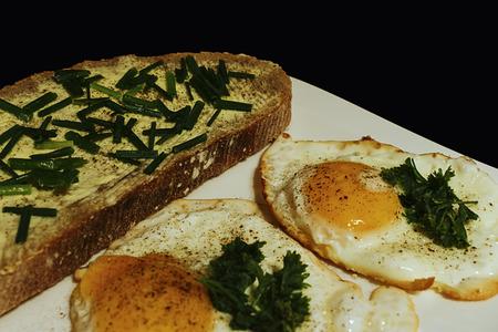 smažená vejce s chlebem a máslem na bílém talíři detailu