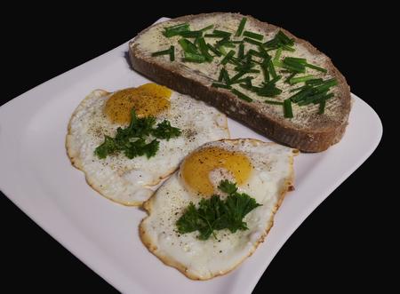 smažená vejce s chlebem a máslem na bílém talíři pohledu