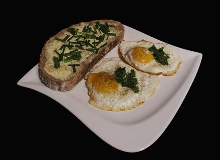 smažená vejce s chlebem a máslem na bílém talíři Reklamní fotografie