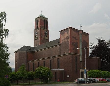 Přijata 28.května 2016 v Jablonci nad Nisou, Česká republika výhledem na kostel, který se nachází na horním náměstí v pozadí oblohy v popředí stromy a kus parkování v přední části kostela