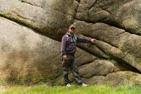 man standing under a rock